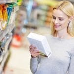 woman reading food label in supermarket